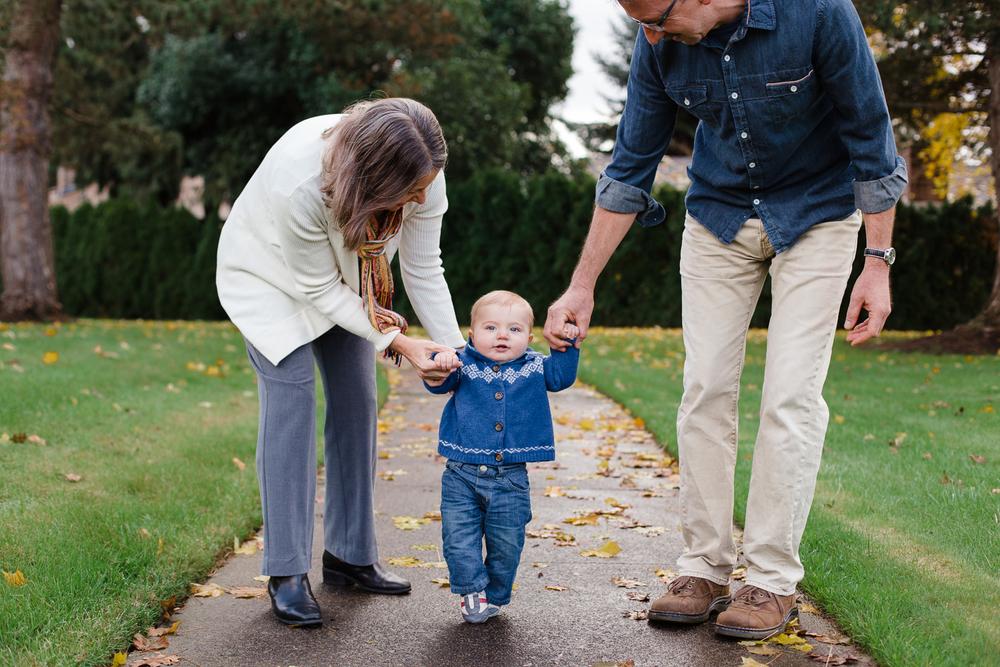 grandma and grandpa walking their grandson