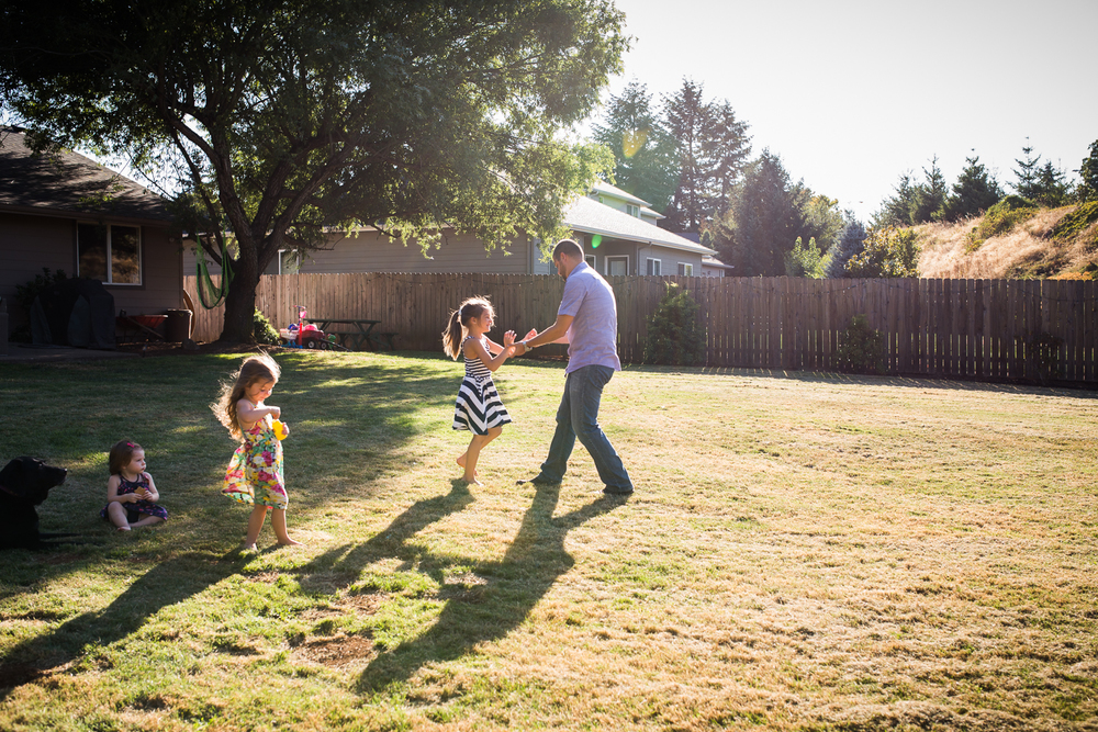 father  playing with his three girls outside