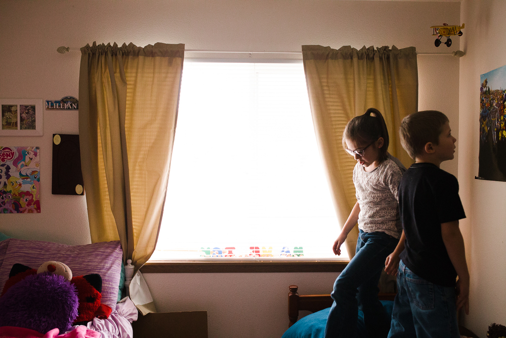 brother and sister standing on a bed
