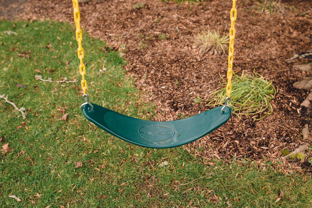 an empty green swing outside