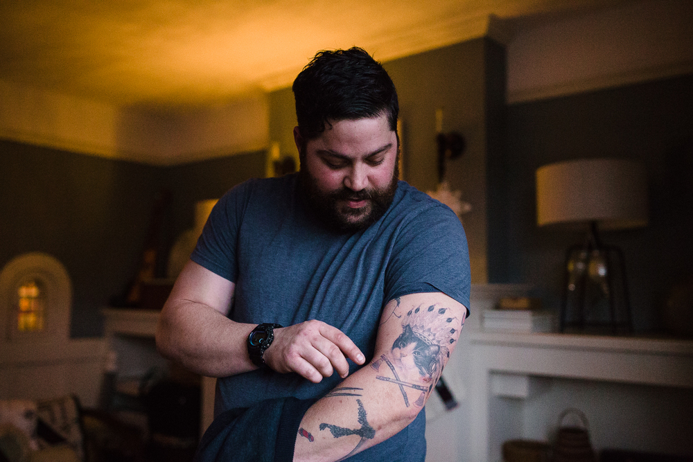 man showing his tattoos on his arm