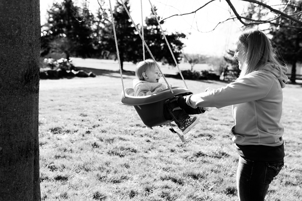 toddler swinging outside with her mom