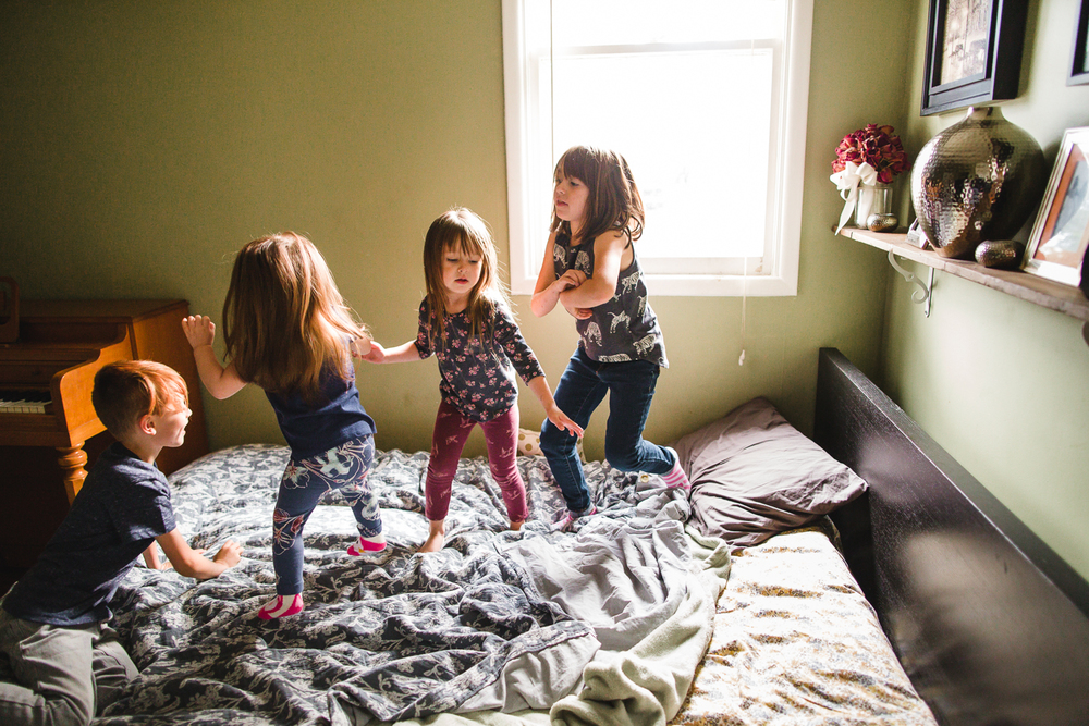 family jumping on bed