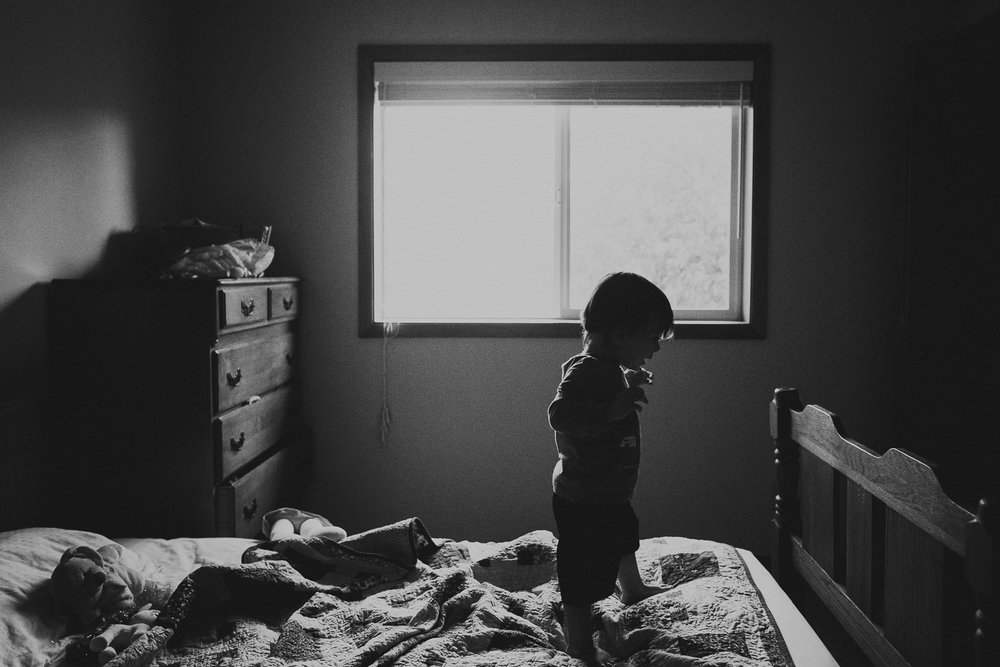 toddler boy walking on bed
