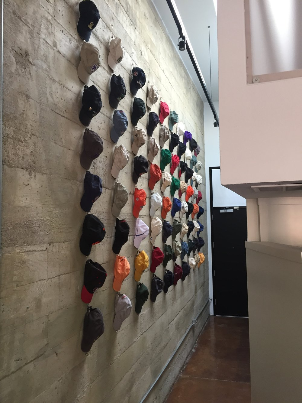 80 hats on a concrete wall