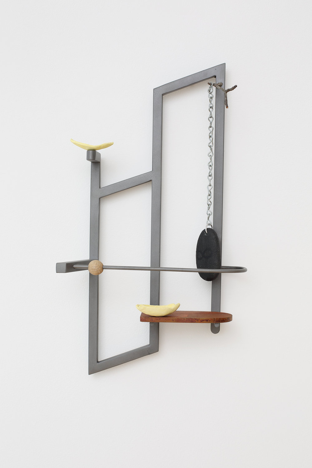 Lesley Jackson ,  Stopping to Rub a Stone , 2017, Steel, lacquer, chain, hand-painted rock, ceramic Frito chips, oak bead, rusted steel shelf