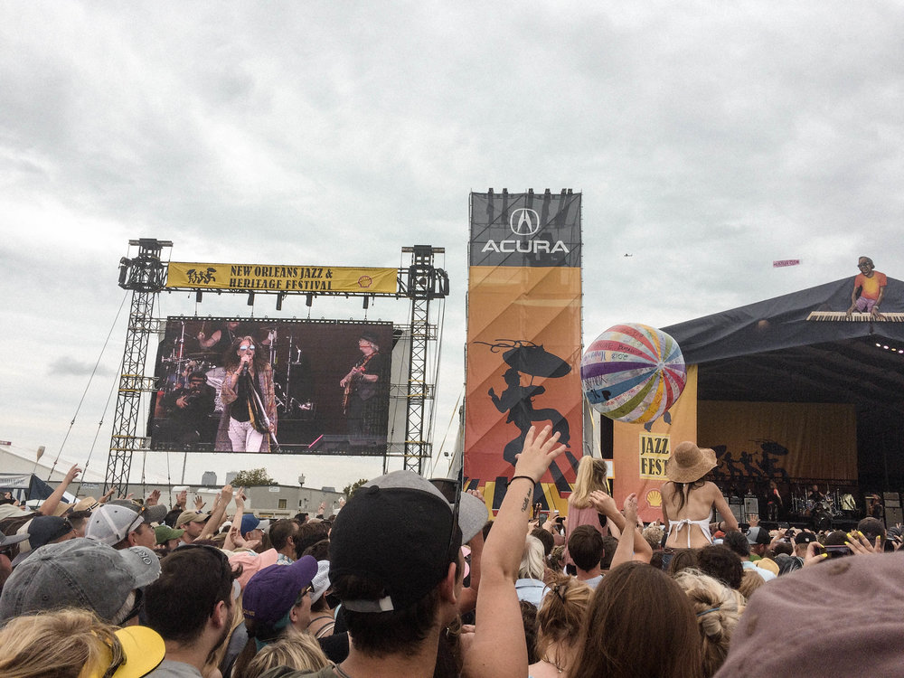 If you've ever held the belief that travel is expensive or solo travel is dangerous and scary - but have secretly wanted to do both - this post is for you!  My solo trip to New Orleans was the Abundant Result of flipping the script on those limiting beliefs! [Aerosmith and Steven Tyler at Jazz Fest in New Orleans]