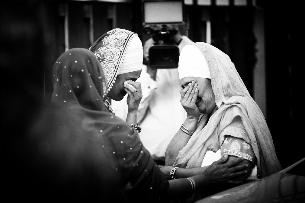 Sad farewell - crying sikh bride with her mother. Photograph from an Asian wedding in Bolton