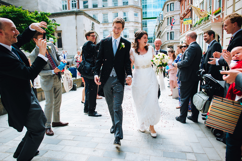 Happy bride and groom finishing the confetti run - Austin Friars London