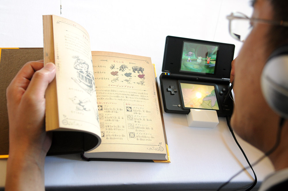 A video game enthusiast plays Ninokuni on the handheld video console   Nintendo   DS on Thursday in Tokyo. The game incorporates a 352-page book of magic to help players beat the game.