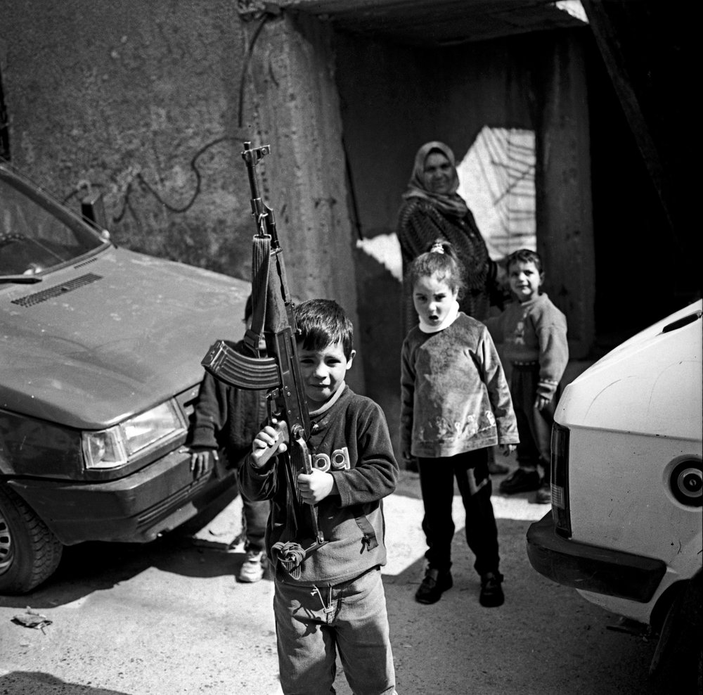 Palestinian kid posing with an assault rifle, Bethlehem 2002.