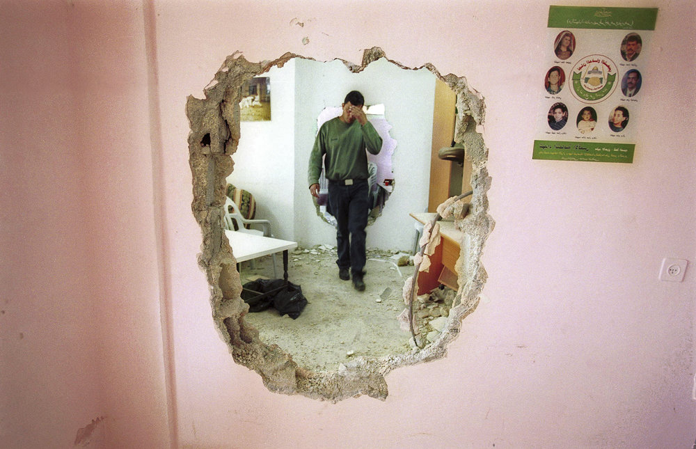 "Operation ""Defensive Shield"", IDF troops moving through party walls using battering rams inside residential buildings, Ramallah, 2002."