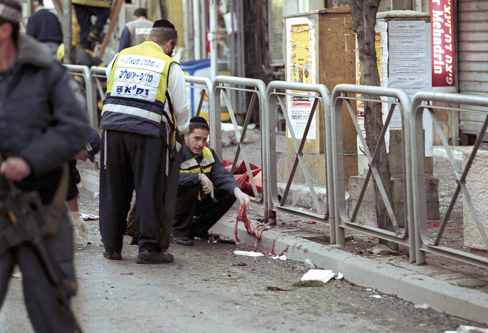 Minutes after a suicide bombing, members of  Zaka (Disaster Victim Identification teams) gathering body parts for proper religious burial, Jerusalem 2002