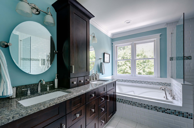 Blue Bathroom with Cherrywood Shaker Cabinets, subway tiles and oval mirror