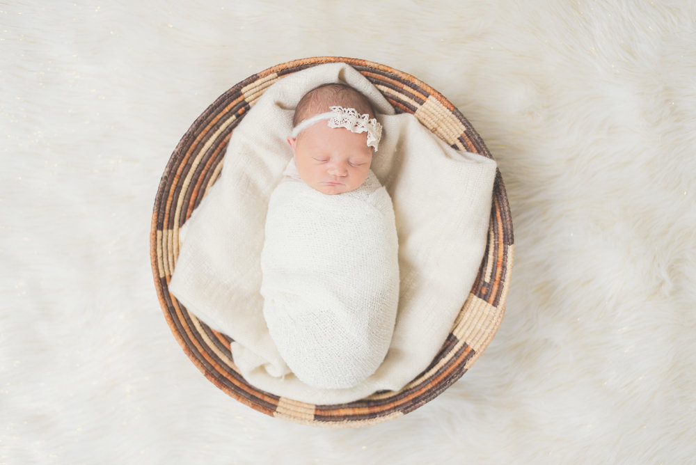baby girl in basket neutral colors