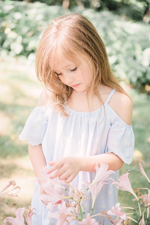 little girl staring at flowers