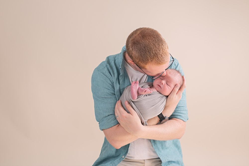 dad kissing newborns head