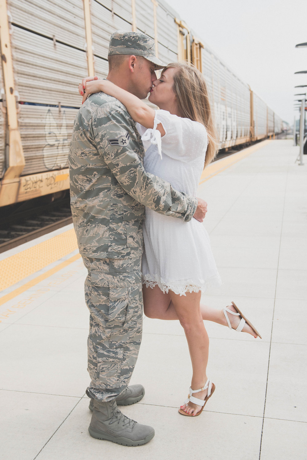 military kiss in front of train