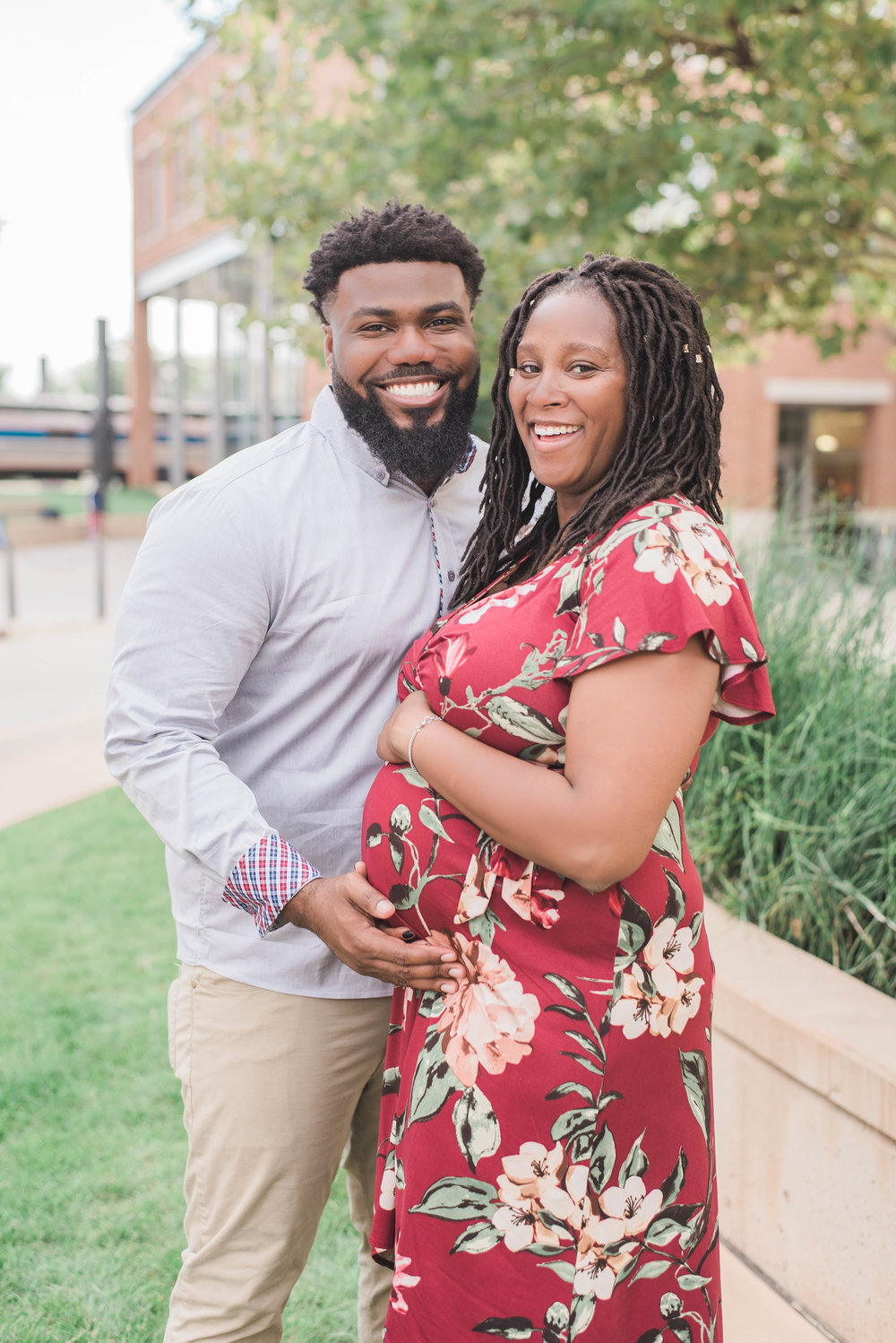 mom and dad in uptown circle maternity photo smiling