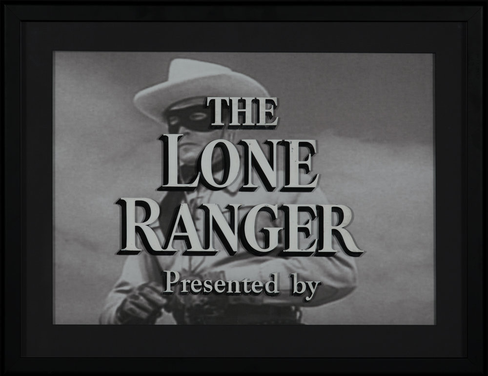 "Original Painted Glass Title Art for The Lone Ranger.  Hand painted, production-used, original glass television title art for ""The Lone Ranger."" The only known surviving title artwork from the legendary television series. Hand painted glass pane, framed in front of a black and white screen image of Clayton Moore. This framed piece is in turn itself framed behind glass, creating a protective exterior and a great visual display. Overall framed size: 21 ¾"" x 28 ¼"". A one of a kind artifact of the golden era of the Hollywood cowboy. Provenance: From Pacific Title Company, Hollywood, CA to current owner.   Lot 215, Brian Lebel's Old West Auction - June 23rd, 2018, Santa Fe, NM. Estimate $30,000-40,000."