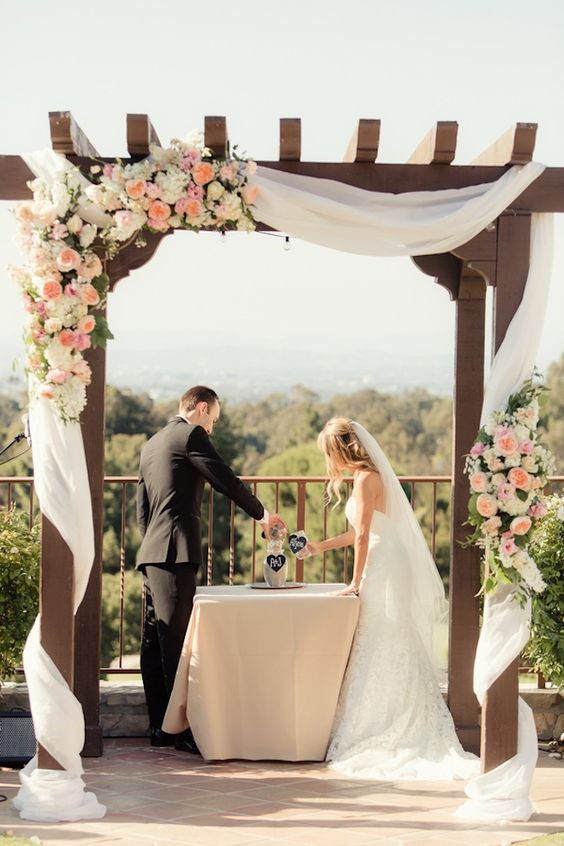 outdoor-wedding-arch-was-draped-with-fabric-and-flurry-of-peach-pink-garden-roses-white-roses-and-chic-greens-via-Figlewicz-Photography.jpg