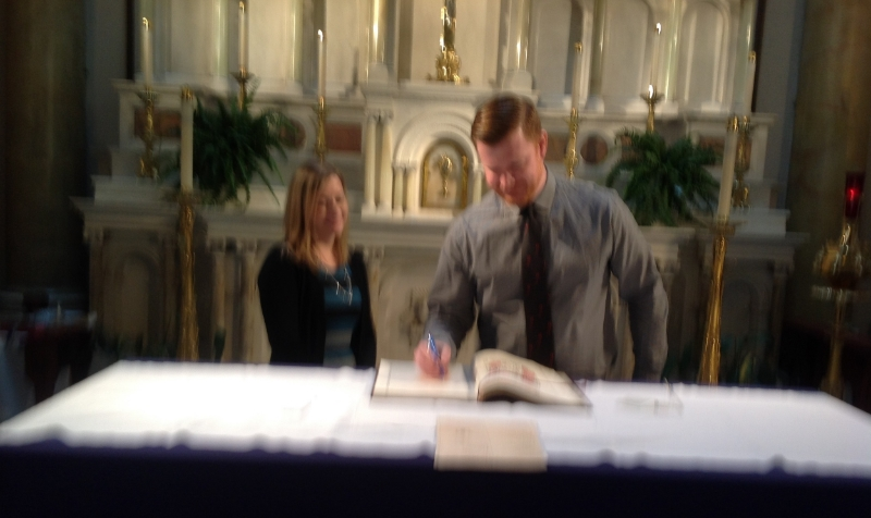 "MATT CURRIER, CATECHUMEN, SIGNING THE ""BOOK OF THE ELECT"""