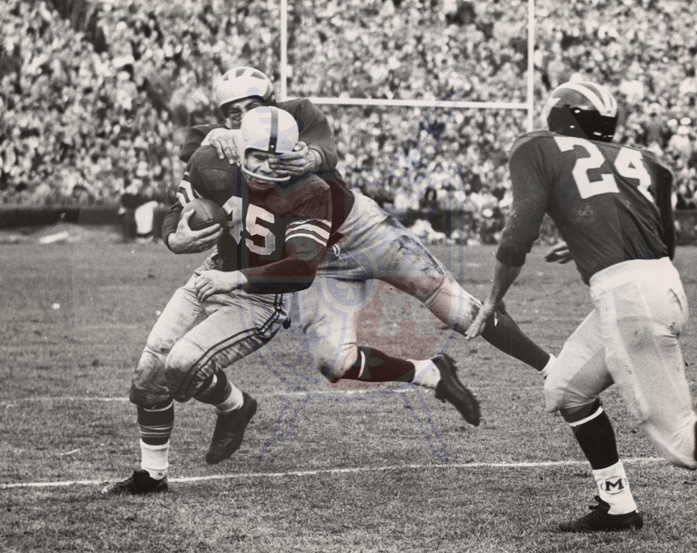 Buckeye halfback #45 Don Sutherin gets an eyeful as a Wolverine gets a handful during this November 19, 1955 edition of the Ohio State versus Michigan rivalry.