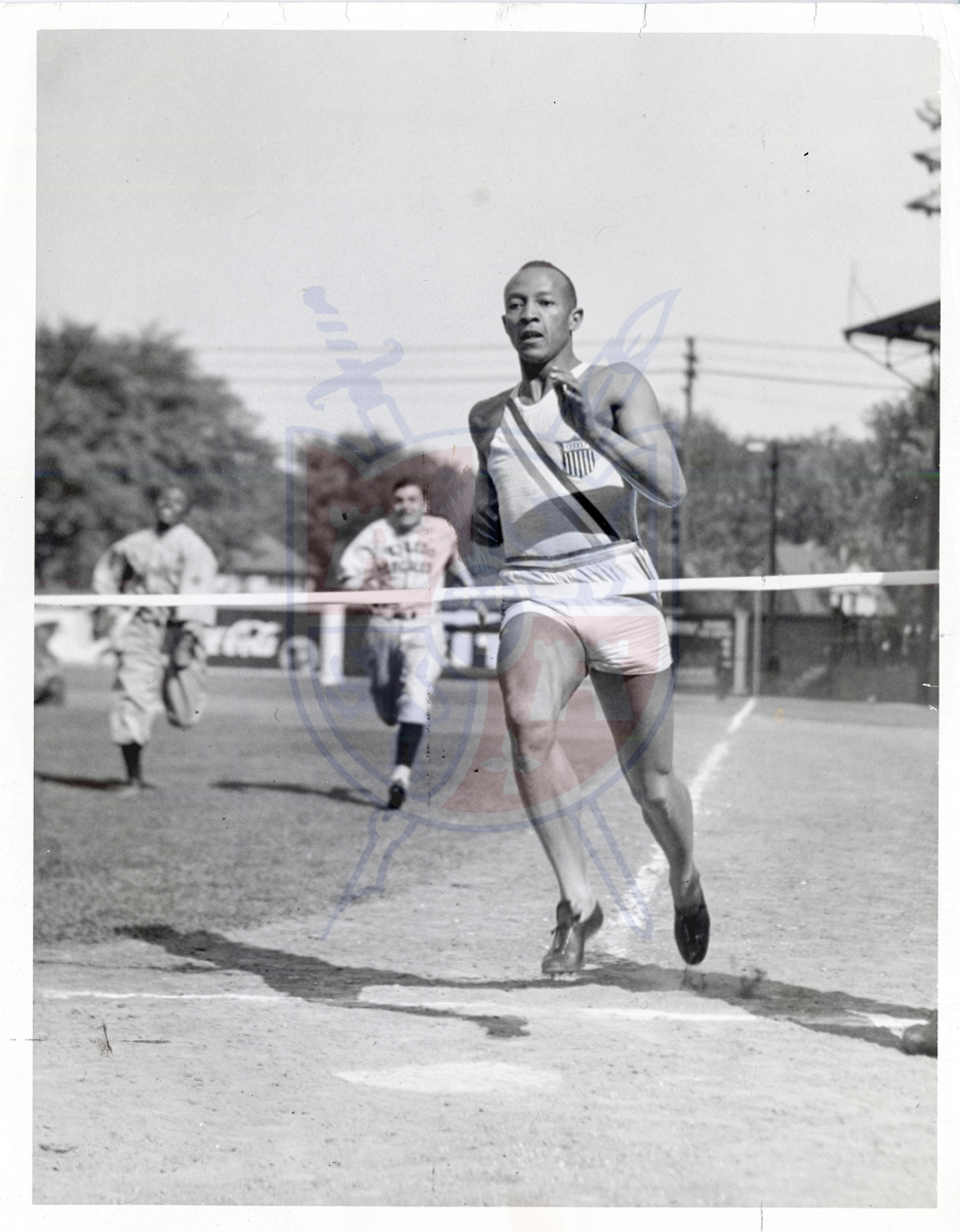 Jesse Owens races members of the Toledo Scales baseball team at Swayne Field on May 8, 1938. He is racing — er, to be more journalistically objective, blowing away — Scales Infielder Elmer Fleck.  Toledo News Bee photographer Jack Winer captured the Olympic gold medalist and cultural icon just before crossing the tape.