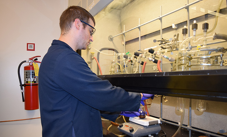 Chemistry Research Associate Jeff Myers demonstrates an experimental procedure inside a fume hood.