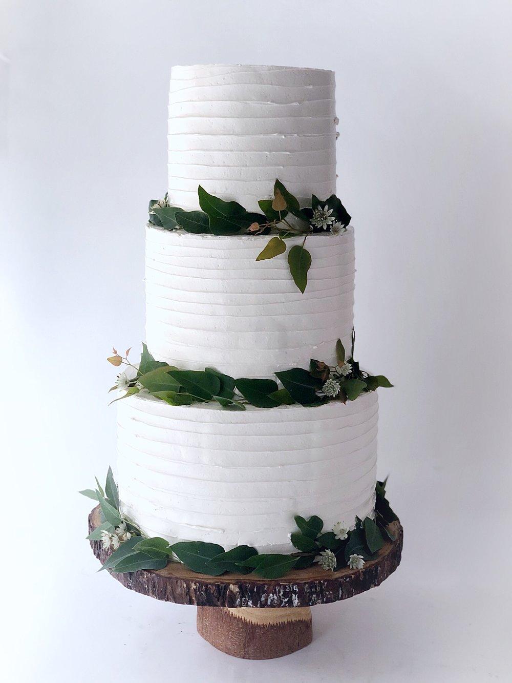 horizontal rustic buttercream cake with greenery