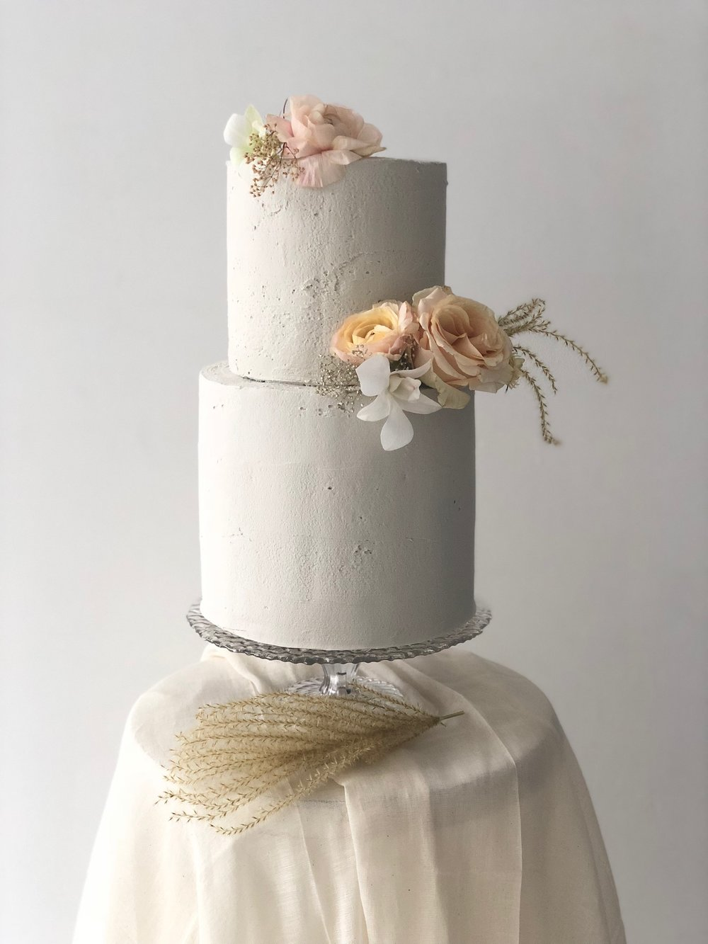 cement textured buttercream cake with flowers