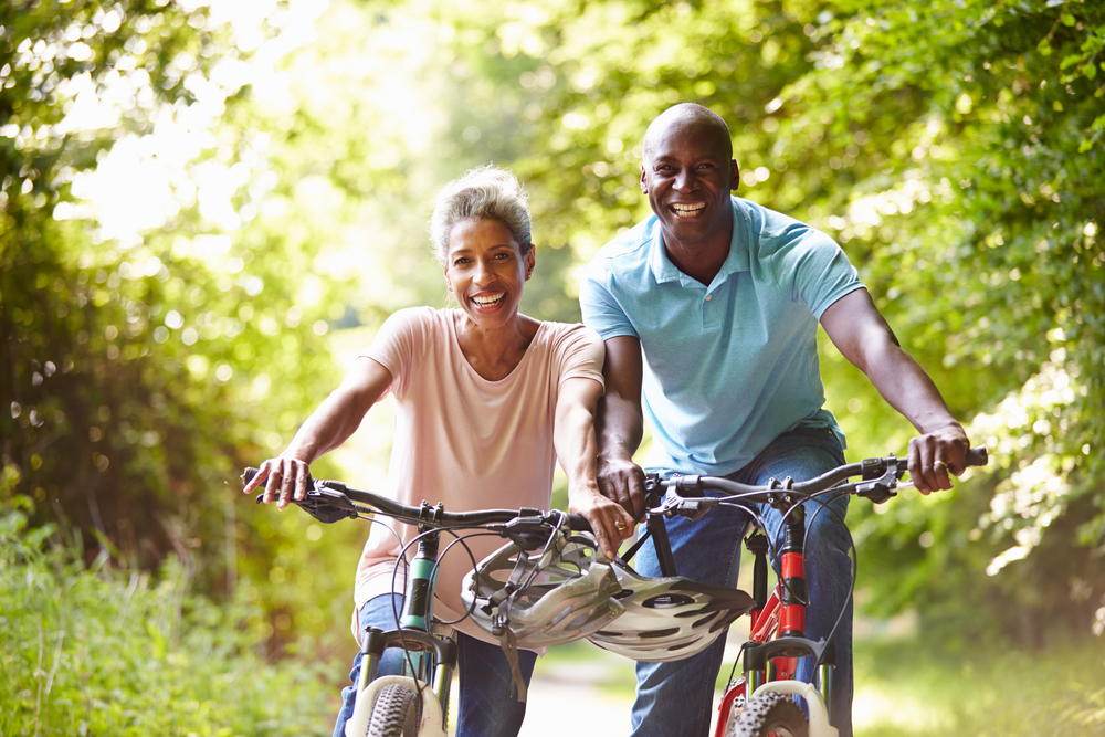 Happy couple on bicycles. Peace of mind comes from effective preventive healthcare.