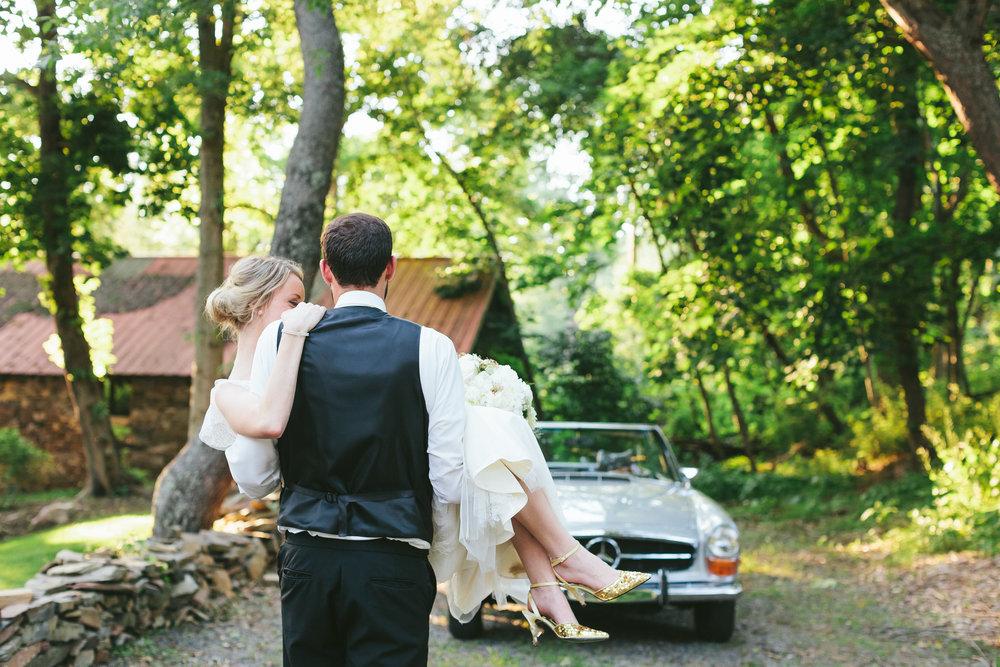 Groom carries Bride away