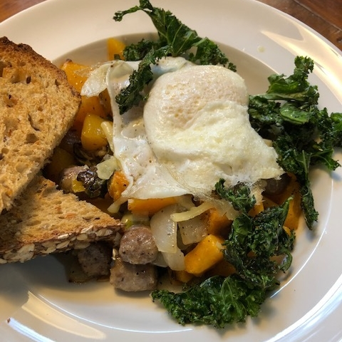 Fall Harvest Bowl: This seasonal bowl features sweet potatoes, butternut squash, onions, and breakfast sausage with crispy kale topped with a fried egg.