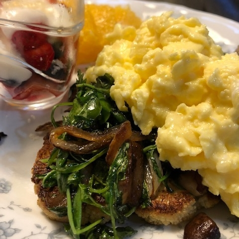 Simply Scrambled: Cooked slow and low, our scrambled eggs have just the right amount of cheese to makes it a favorite. Paired with fried polenta topped with wilted greens and sautéed mushrooms.