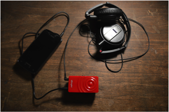 Vibrotactile Interface: personal device (smartphone), wearable bass shaker (Woojer) & headphones. Photo by Jessica Rajko.