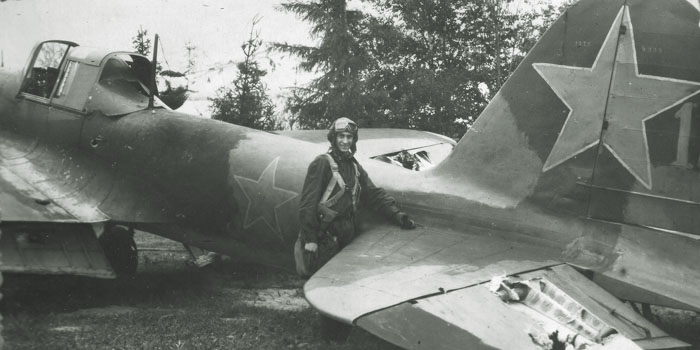 A pilot poses with his damaged Il-2 following a mission. In this instance, flak has damaged the elevator.