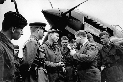 A group of Il-2 pilots discuss the results of a mission after landing.