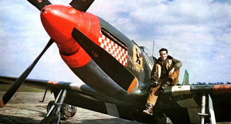 CAPTAIN DON GENTILE POSES WITH HIS P-51B MUSTANG IN THE SPRING OF 1944. AFTER SERVING WITH ONE OF  THE RAF'S EAGLE SQUADRONS (COMPOSED OF AMERICAN VOLUNTEERS) AND SHOOTING DOWN TWO AIRCRAFT, GENTILE TRANSFERRED TO THE USAAF, EVENTUALLY FLYING WITH THE 4TH FIGHTER GROUP. DURING EARLY 1944, WHILE FLYING THE MUSTANG, HE SHOT DOWN 15.5 ENEMY PLANES, MAKING HIM THE HIGHEST-SCORING ACE IN 8TH AIR FORCE AT THE TIME. SOURCE: WIKIPEDIA.