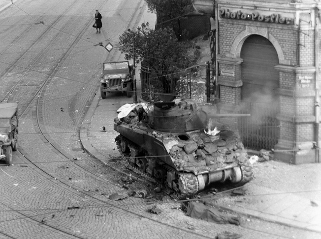A scene that became all-to-familiar to Allied soldiers in Europe- a Sherman ablaze. Photo source: Wikipedia.