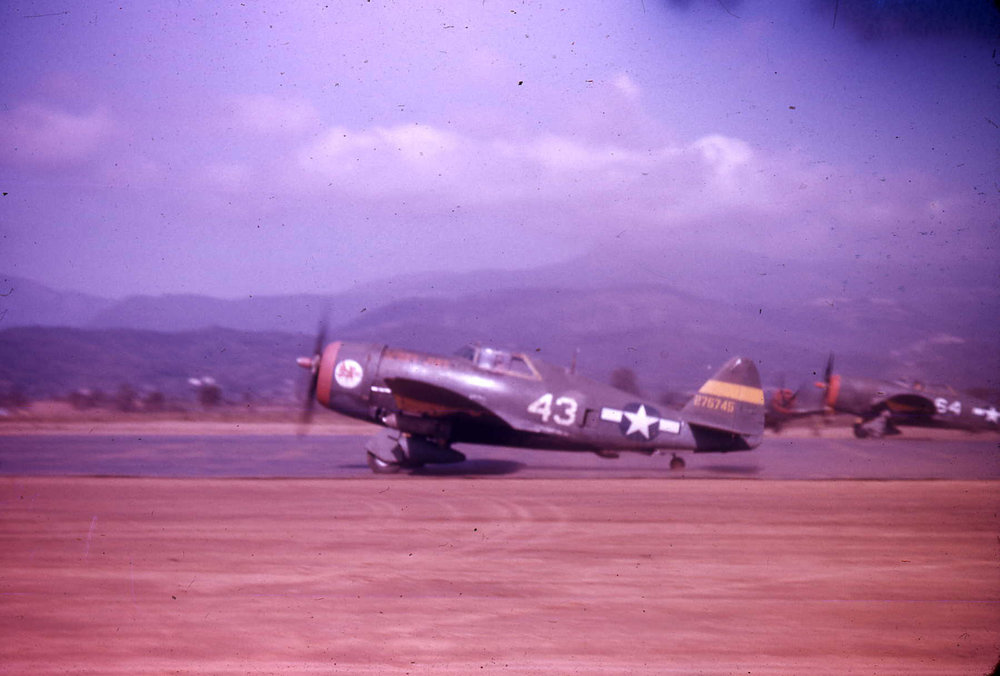 Two P-47Ds from the 65th Fighter Squadron take off for a ground attack mission in Italy from their base in Corsica. This squadron along with others in Corsica participated in a vigorous interdiction campaign in central and northern Italy called Operation Strangle, the goal of which was to cut off German front lines from their supply lines. Photo source: American Air Museum.