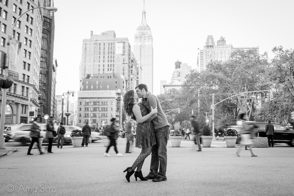 Couple shares a kiss on a busy New York street with Empire State Building in background | Madison Square Park Engagement | NYC Engagement | Ashley & Nick's Engagement | Amy Sims Photography