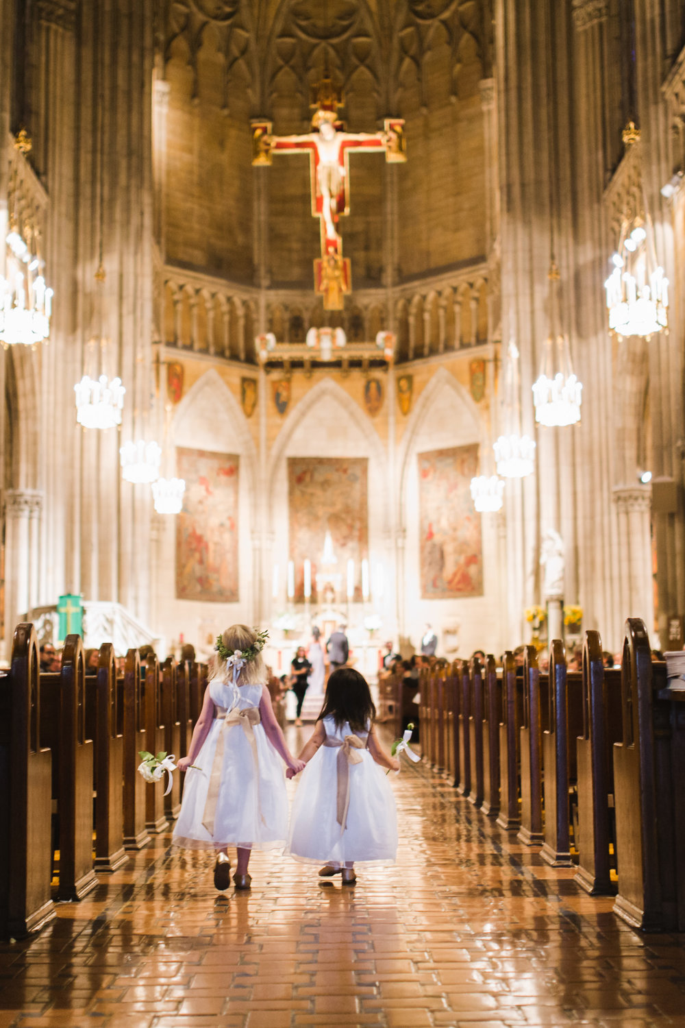 @Amy Sims Photography | New York Wedding Photography | Flowergirls hold hands down aisle of church