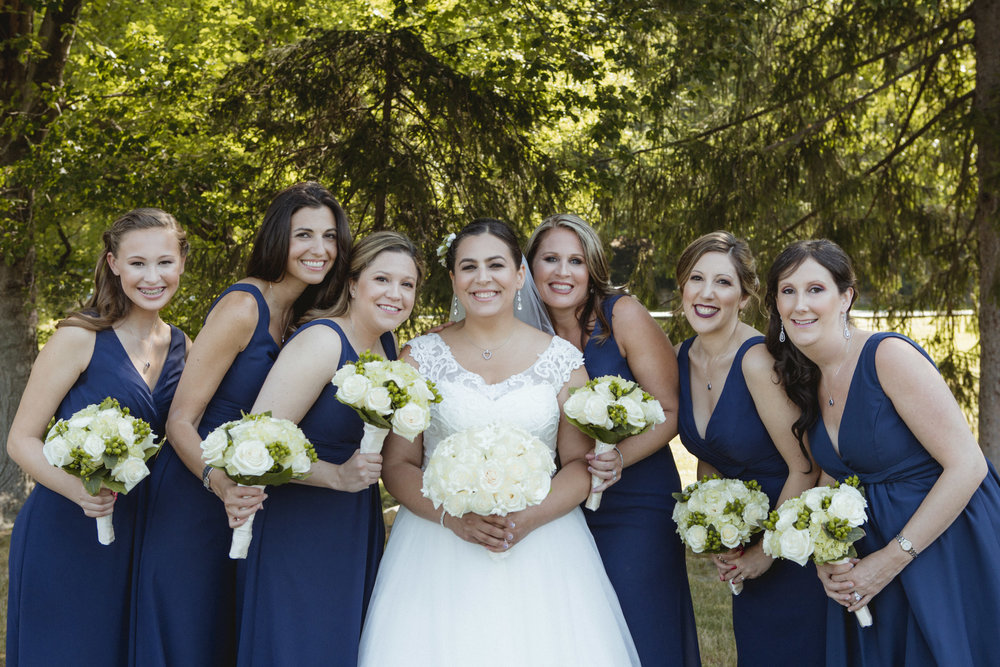 Bride wears lace, scoop neck gown, bridesmaids wear navy, floor length gowns from Alexia Designs. White & green bouquets from Arcadia Florists - New Rochelle wedding - New York wedding - Hudson Valley wedding - Heather & Ian's wedding - Amy Sims Photography