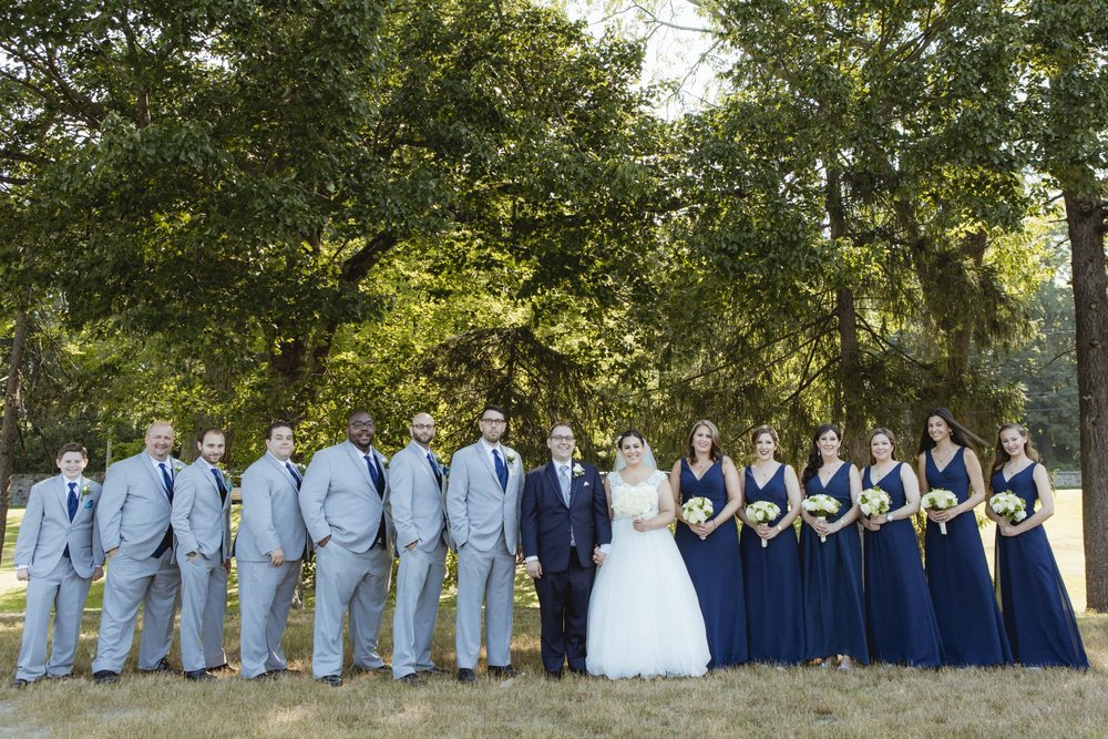 Wedding Party poses in Navy and Grey - Bride wears lace gown, bridesmaids wear navy, floor length gowns from Alexia Designs. White & green bouquets from Arcadia Florists - New Rochelle wedding - New York wedding - Hudson Valley wedding - Heather & Ian's wedding - Amy Sims Photography