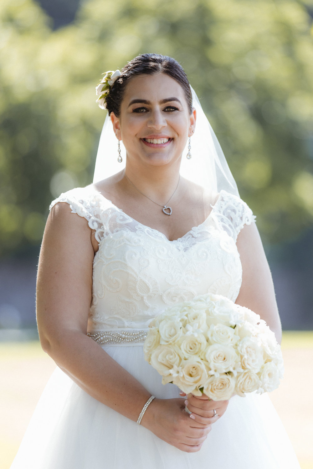 Bride beams in lace, scoop neck gown, with accent belt, bouquet from Arcadia Florist - Bride wears lace gown, bridesmaids wear navy, floor length gowns from Alexia Designs. White & green bouquets from Arcadia Florists - New Rochelle wedding - New York wedding - Hudson Valley wedding - Heather & Ian's wedding - Amy Sims Photography