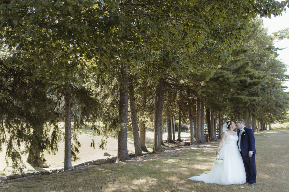 Couple leans in for a kiss under a line of trees on a sunny day - Bride wears lace gown, bridesmaids wear navy, floor length gowns from Alexia Designs. White & green bouquets from Arcadia Florists - New Rochelle wedding - New York wedding - Hudson Valley wedding - Heather & Ian's wedding - Amy Sims Photography