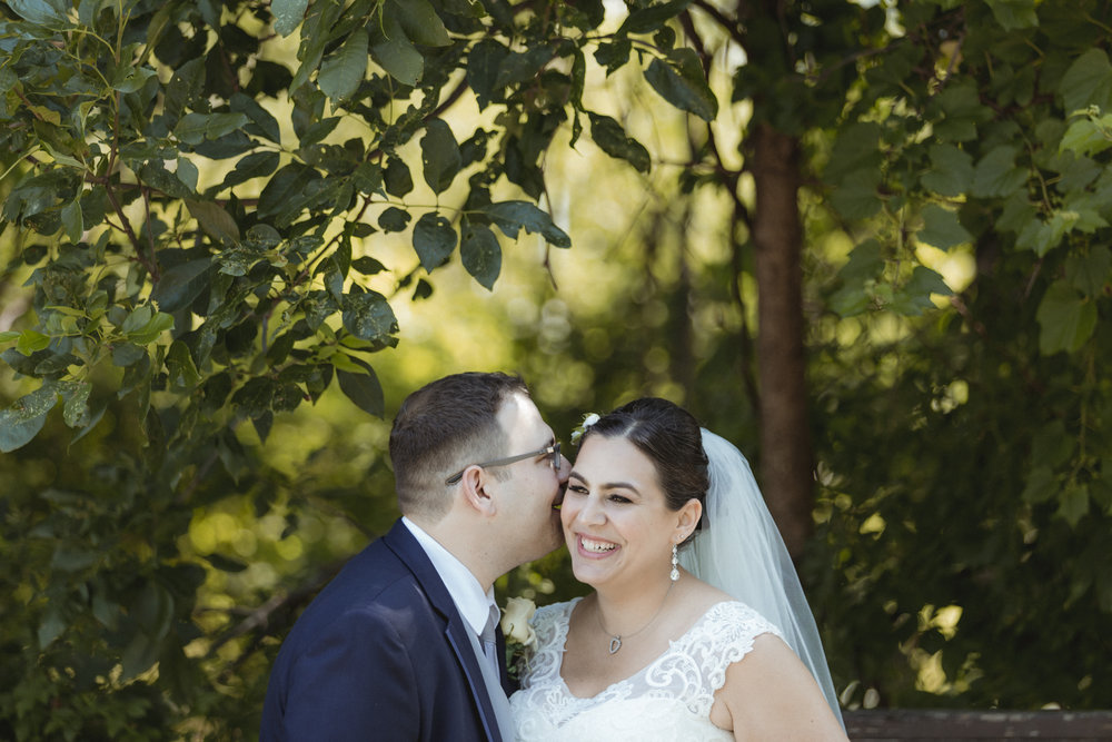 Groom whispers in Brides ear while she giggles - Bride wears lace gown, bridesmaids wear navy, floor length gowns from Alexia Designs. White & green bouquets from Arcadia Florists - New Rochelle wedding - New York wedding - Hudson Valley wedding - Heather & Ian's wedding - Amy Sims Photography