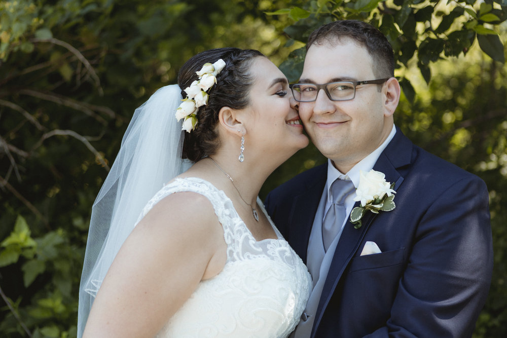 Bride nuzzles her nose against groom's cheek - Bride wears lace gown, bridesmaids wear navy, floor length gowns from Alexia Designs. White & green bouquets from Arcadia Florists - New Rochelle wedding - New York wedding - Hudson Valley wedding - Heather & Ian's wedding - Amy Sims Photography