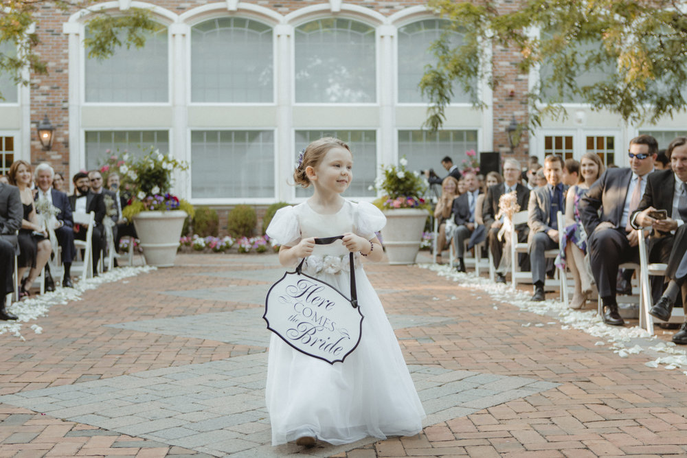 "Flowergirl walks down the aisle holding ""here comes the bride"" sign - Estate at Florentine Gardens wedding - Hudson Valley Wedding - Kelsey & Anish's wedding - Amy Sims Photography"